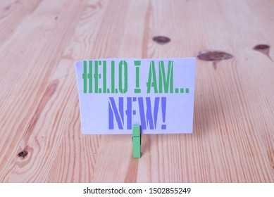 Writing note showing Hello I Am New. Business photo showcasing used as greeting or to begin telephone conversation Wooden floor background green clothespin groove slot office.