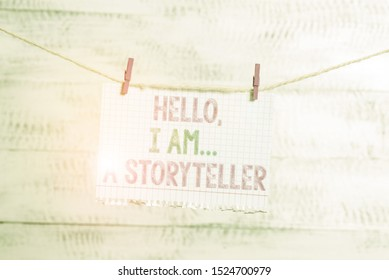 Writing note showing Hello I Am A Storyteller. Business photo showcasing introducing yourself as novels article writer Clothesline clothespin rectangle shaped paper reminder white wood desk.