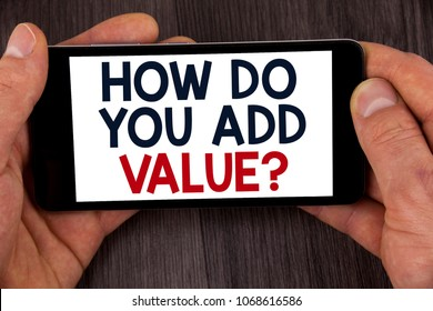 Writing note showing  How Do You Add Value Question. Business photo showcasing Bring business progress contribute earn written Mobile Phone Screen holding by man the wooden background.
