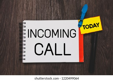 Writing note showing Incoming Call. Business photo showcasing Inbound Received Caller ID Telephone Voicemail Vidcall Open notebook white page clothespin holding reminder wooden background.