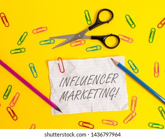 Writing note showing Influencer Marketing. Business photo showcasing Endorser who Influence Potential Target Customers Crushed striped paper sheet scissors pencils clips colored background.
