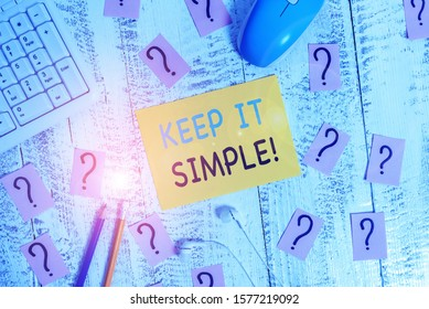 Writing note showing Keep It Simple. Business photo showcasing ask something easy understand not go into too much detail Writing tools and scribbled paper on top of the wooden table.