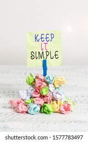 Writing note showing Keep It Simple. Business photo showcasing Easy to toss around Understandable Generic terminology Reminder pile colored crumpled paper clothespin wooden space.