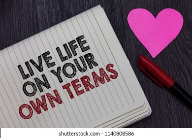 Writing note showing Live Life On Your Own Terms. Business photo showcasing Give yourself guidelines for a good living Strikethrough words on notepad love heart pen on blackish woody desk.