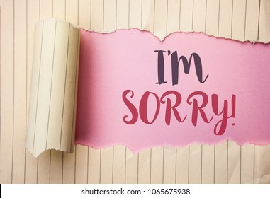 Writing note showing  I m Sorry. Business photo showcasing Apologize Conscience Feel Regretful Apologetic Repentant Sorrowful written on the pink background behind Tear Notebook Paper.
