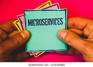Writing note showing Microservices. Business photo showcasing Software development technique Decomposing an application Small multi colour notes hand border plane background remember card.
