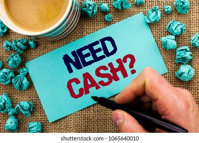Writing note showing  Need Cash Question. Business photo showcasing Wealth Question Needy Currency Money Advice Conceptual written by Man Holding Pen on Sticky Note Paper the jute background Cup