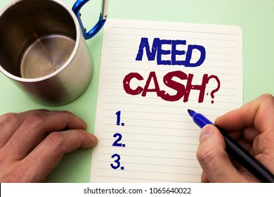 Writing note showing  Need Cash Question. Business photo showcasing Wealth Question Needy Currency Money Advice Conceptual written by Man on Notebook Paper Holding Marker on plain background Cup.