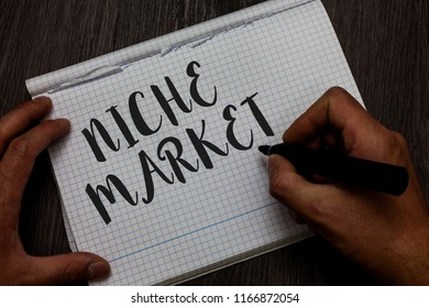 Writing note showing Niche Market. Business photo showcasing Subset of the market on which specific product is focused Man hand holding marker communicating ideas reflections squared paper.