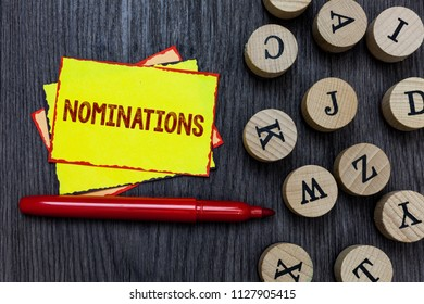 Writing note showing Nominations. Business photo showcasing Suggestions of someone or something for a job position or prize Multiple small sticky cards wood alphabet button pen grey background.