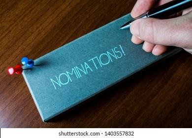 Writing note showing Nominations. Business photo showcasing action of nominating or state being nominated for prize Close up left man right hand holding pen fixed pins lying wooden table.