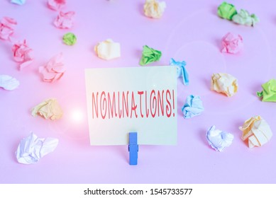 Writing note showing Nominations. Business photo showcasing action of nominating or state being nominated for prize Colored crumpled papers empty reminder pink floor background clothespin.