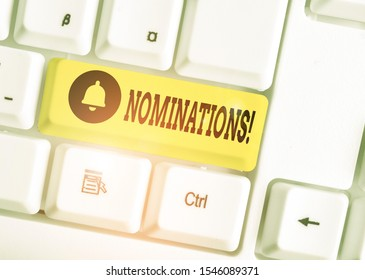 Writing note showing Nominations. Business photo showcasing action of nominating or state being nominated for prize White pc keyboard with note paper above the white background.