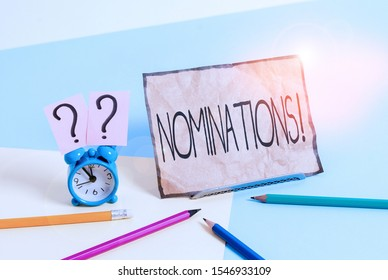 Writing note showing Nominations. Business photo showcasing action of nominating or state being nominated for prize Mini size alarm clock beside stationary on pastel backdrop.