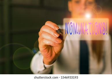 Writing note showing Nominations. Business photo showcasing action of nominating or state being nominated for prize Blurred woman in the background pointing with finger in empty space.