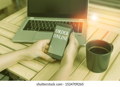 Writing note showing Order Online. Business photo showcasing activity of buying products or services over the Internet woman with laptop smartphone and office supplies technology.
