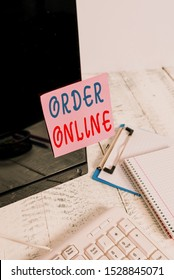 Writing note showing Order Online. Business photo showcasing activity of buying products or services over the Internet Note paper taped to black computer screen near keyboard and stationary.
