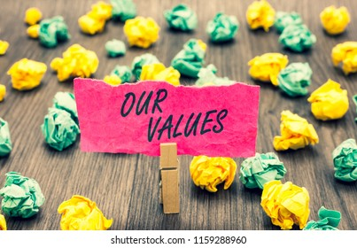 Writing note showing Our Values. Business photo showcasing list of morals companies or individuals commit to do them Clothespin holding pink note paper crumpled papers several tries.