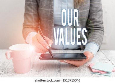 Writing note showing Our Values. Business photo showcasing list of morals companies or individuals commit to do them Business woman sitting with mobile phone and cup of coffee on the table.