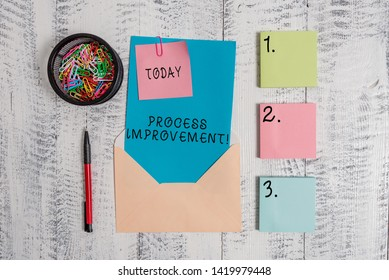Writing note showing Process Improvement. Business photo showcasing Optimization Meet New Quotas Standard of Quality Envelope letter sticky note ballpoint clips on wooden background.