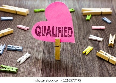 Writing note showing Qualified. Business photo showcasing Officially trained to perform a particular job Certified Clothespin holding pink paper heart several clothespins wooden floor.