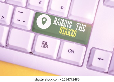 Writing note showing Raising The Stakes. Business photo showcasing Increase the Bid or Value Outdo current bet or risk White pc keyboard with note paper above the white background.