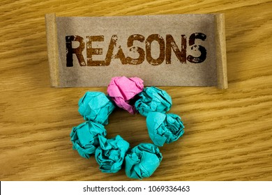 Writing note showing  Reasons. Business photo showcasing Causes Explanations Justifications for an action or event Motivation written on Folded Cardboard Paper Piece wooden background Paper Balls