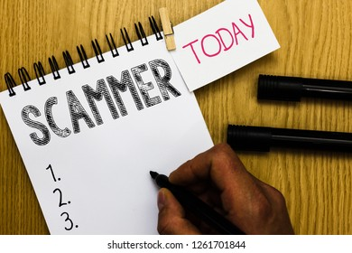 Writing note showing Scammer. Business photo showcasing Someone who makes money by tricking showing Crime Fraud Thief Man holding marker notebook clothepin reminder wooden table cup coffee.