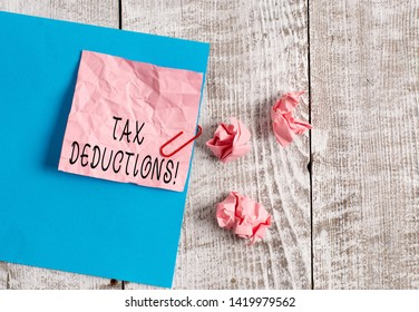 Writing note showing Tax Deductions. Business photo showcasing reduction income that is able to be taxed of expenses Wrinkle paper and cardboard placed above wooden background.
