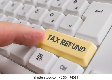 Writing note showing Tax Refund. Business photo showcasing refund on tax when the tax liability is less than the tax paid White pc keyboard with note paper above the white background.