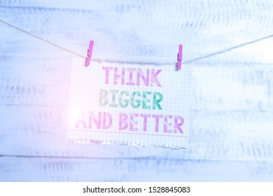 Writing note showing Think Bigger And Better. Business photo showcasing no Limits be Open minded Positivity Big Picture Clothesline clothespin rectangle shaped paper reminder white wood desk.