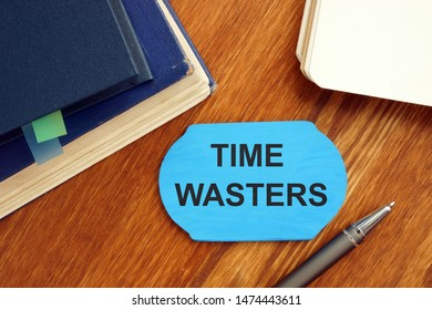 Writing note showing time wasters. The text is written on a small wooden board. Books, pen, notebook, wooden background are on the photo.
