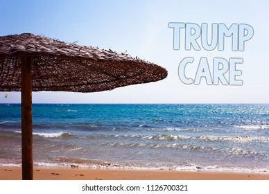 Writing note showing  Trump Care. Business photo showcasing refers to replacement for Affordable Care Act in united states Blue beach sand message idea sunshade water sky natural landscape.