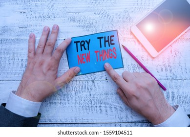 Writing note showing Try The New Things. Business photo showcasing Breaks up Life Routine Learn some Innovative Skills Hand hold note paper near writing equipment and smartphone.
