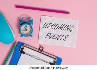 Writing note showing Upcoming Events. Business photo showcasing the approaching planned public or social occasions Alarm clock clipboard paper sheets mouse markers colored background.