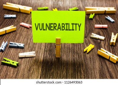 Writing note showing Vulnerability. Business photo showcasing Information susceptibility systems bug exploitation attacker Clips art board creative ideas paper paperclip holding wood shadow.