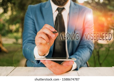 Writing note showing Warning Nosebleed. Business photo showcasing caution on bleeding from the blood vessels in the nose Businessman pointing with pen in empty copy space.