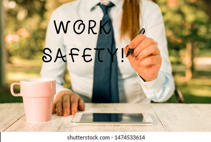 Writing note showing Work Safety. Business photo showcasing policies and procedures in place to ensure health of employees Female business person sitting by table and holding mobile phone.