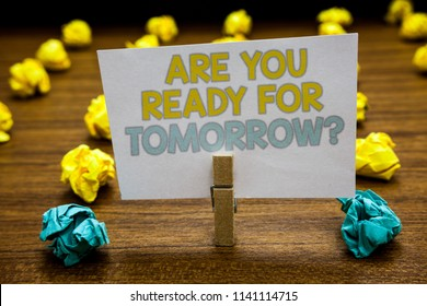 Writing note showing Are You Ready For Tomorrow question. Business photo showcasing Preparation to the future Motivation Written notepad stand with paperclip yellow blue lobs on wooden deck.