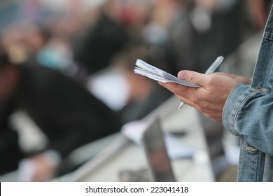 writing notebook reporter in a stadium