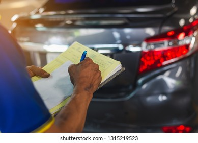 Writing on clipboard while insurance agent examining car after accident