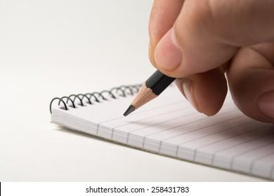 Writing on notepad. close up, isolated on white background
