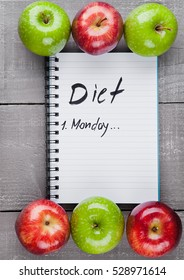 Writing pad with healthy apples as diet plan idea on wooden board