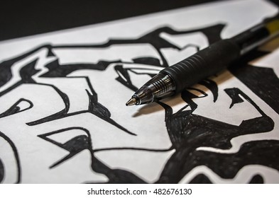 Writing pen resting on black and white graffiti artwork drawing.