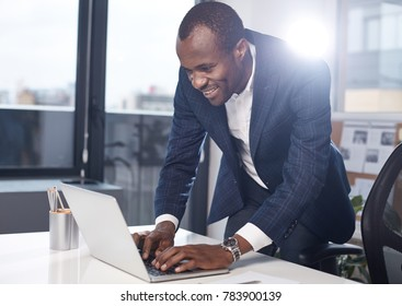 Writing project. Cheerful successful adult african businessman in suit is typing on laptop with smile. He is standing in office while leaning over table and working on gadget. Big window in background