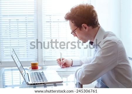 writing resume, young handsome business man working in office