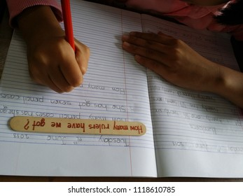 Writing skill practice; hand writing with a  pencil, write the sentences from the ice cream stick, hand writing of a small kid in the second grade, neatly writing on a notebook.