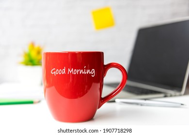 Writing Text Good Morning on the red cup.  Take Care for healthy life office.  Close Coffee cup for relaxation  and break time, laptop background.  Lifestyle Health Concept