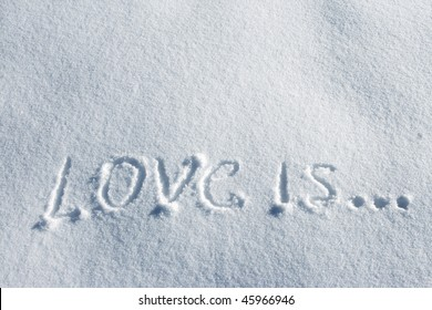 writing text LOVE IS on the snow