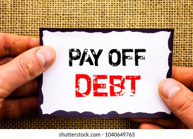 Writing text showing  Pay Off Debt. Concept meaning Reminder To Paying Owed Financial Credit Loan Bills written Sticky Note Paper Holding Hand with Finger.